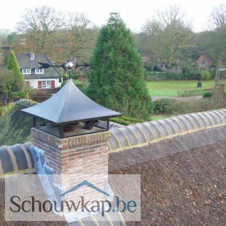 Een getoogde schoorsteenkap met gaas en een windwijzer wereldbol