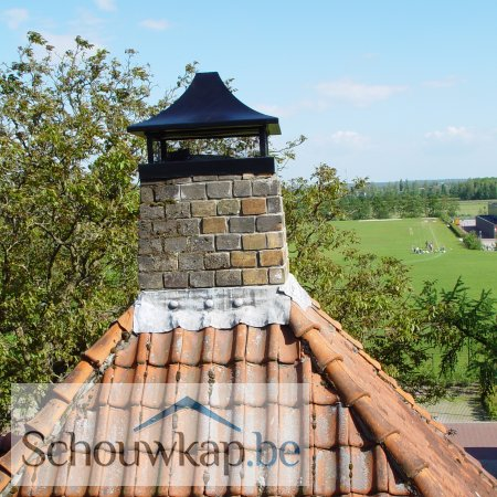 Een getoogde schoorsteenkap met afdekrand op de punt van het dak!